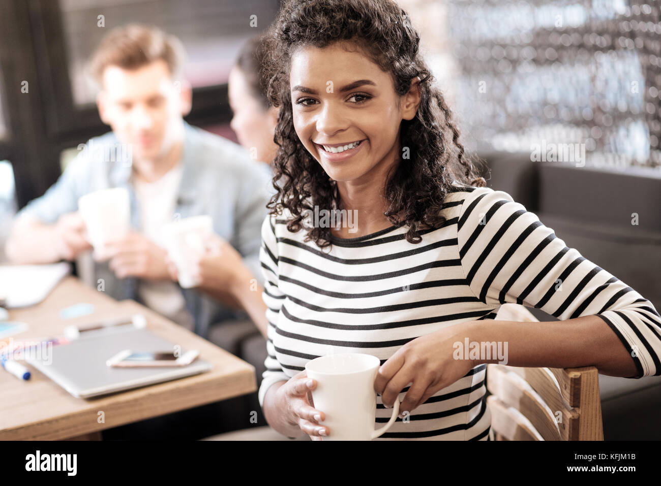 Glad curly-haired dark-eyed girl sitting at the table - Stock Image