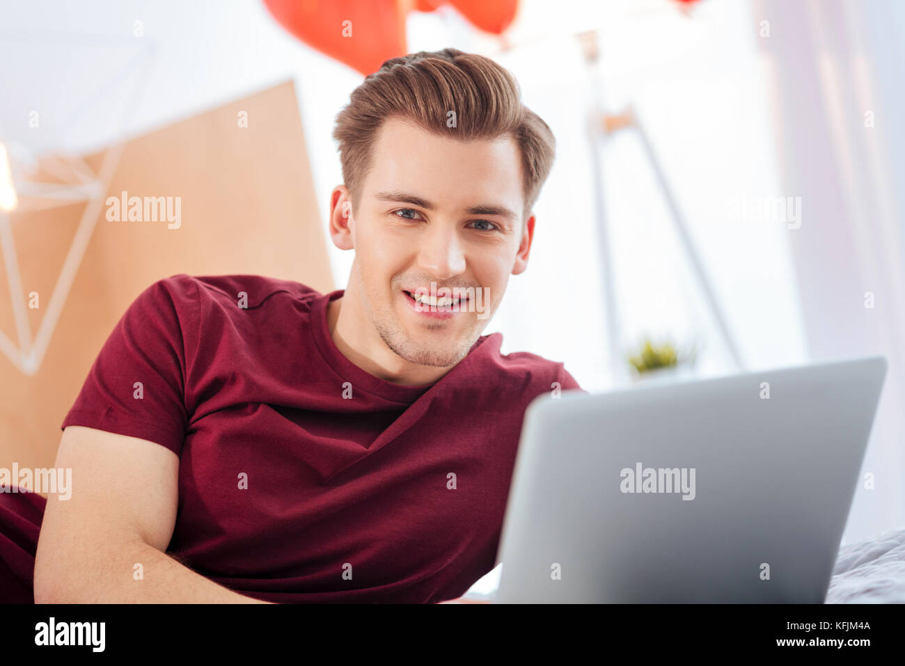 Handsome gentleman looking into camera with cheerful smile - Stock Image