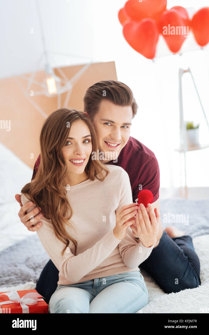 Excited gentleman embracing girlfriend after proposal - Stock Image