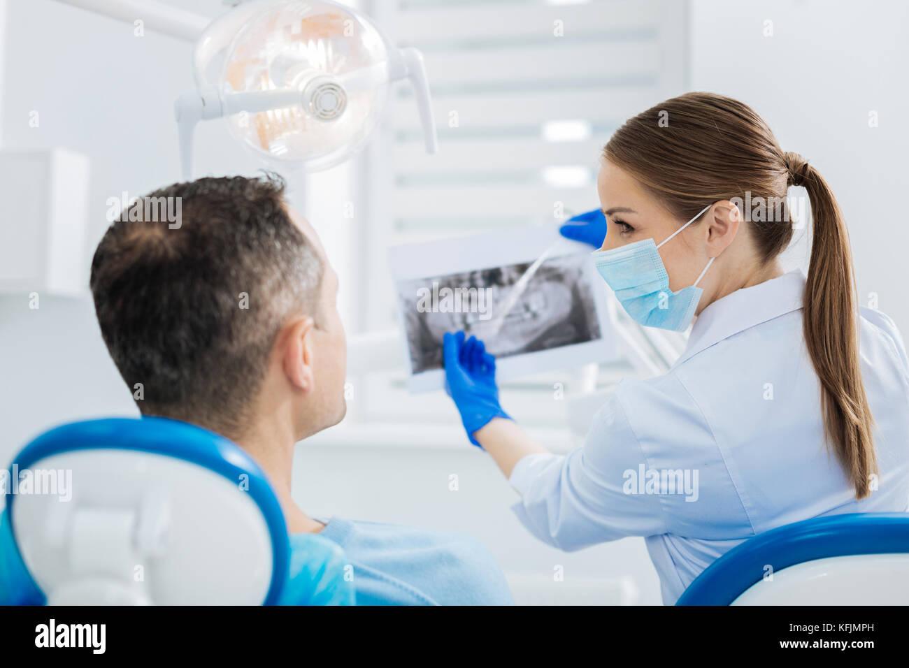 Nice joyful dentist pointing at the Xray photo - Stock Image
