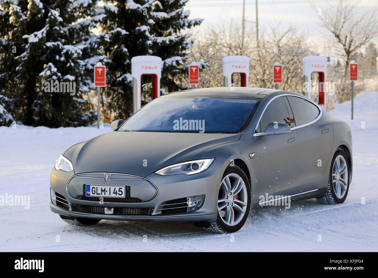 PAIMIO, FINLAND - JANUARY 17, 2016: Unidentified man drives Tesla Model S at Supercharger Station Paimio on a cold - Stock Image