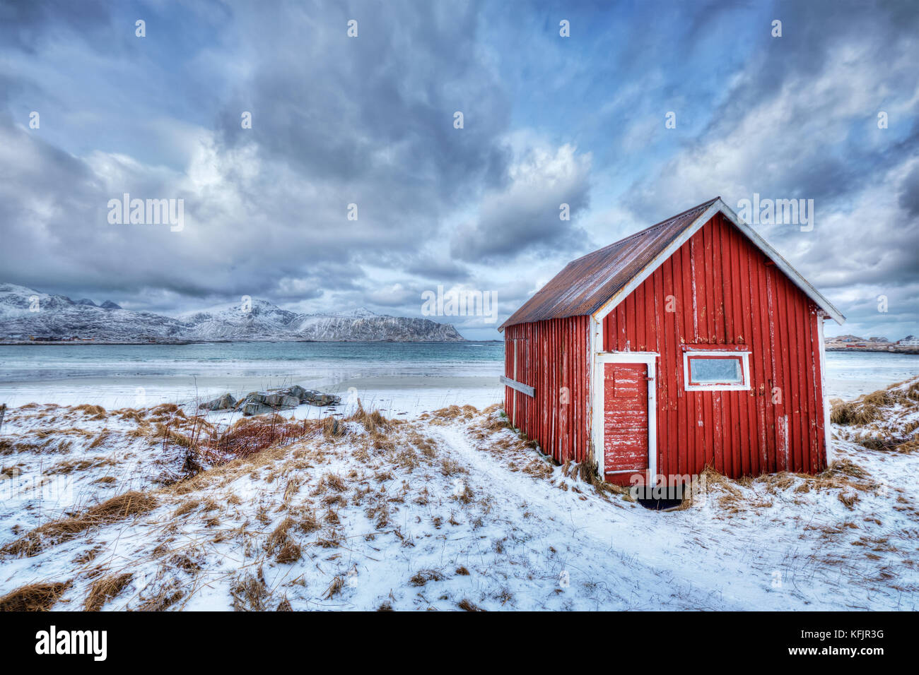 Red rorbu house shed on beach of fjord, Norway - Stock Image