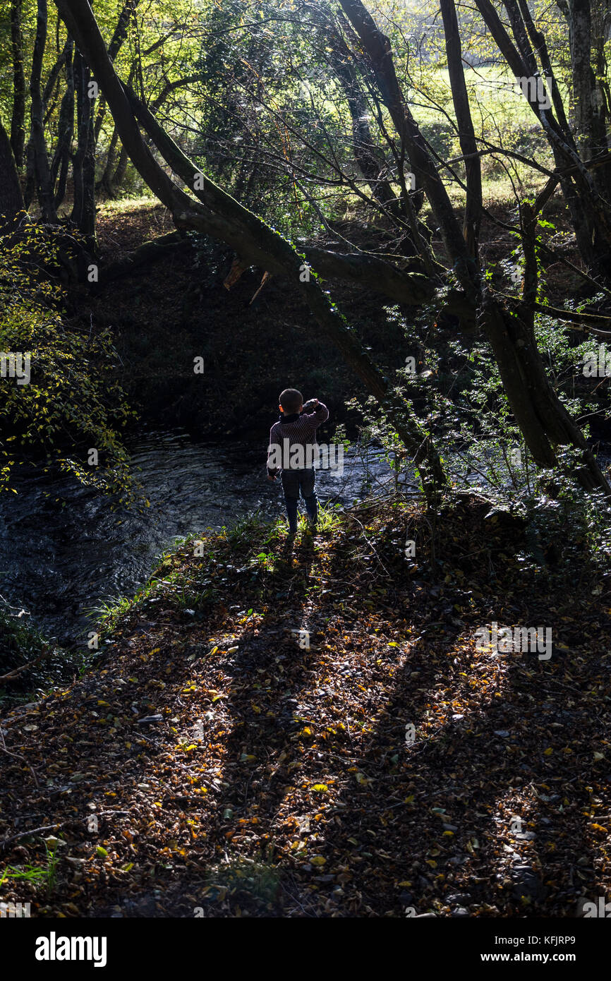 young boy playing poo sticks in the river Teign,Poohsticks is a sport fmentioned in The House at Pooh Corner, a - Stock Image