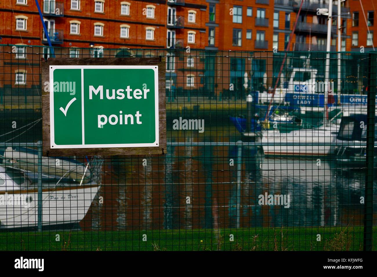 Green muster point sign at Ipswich marina on a bright autumn afternoon. - Stock Image