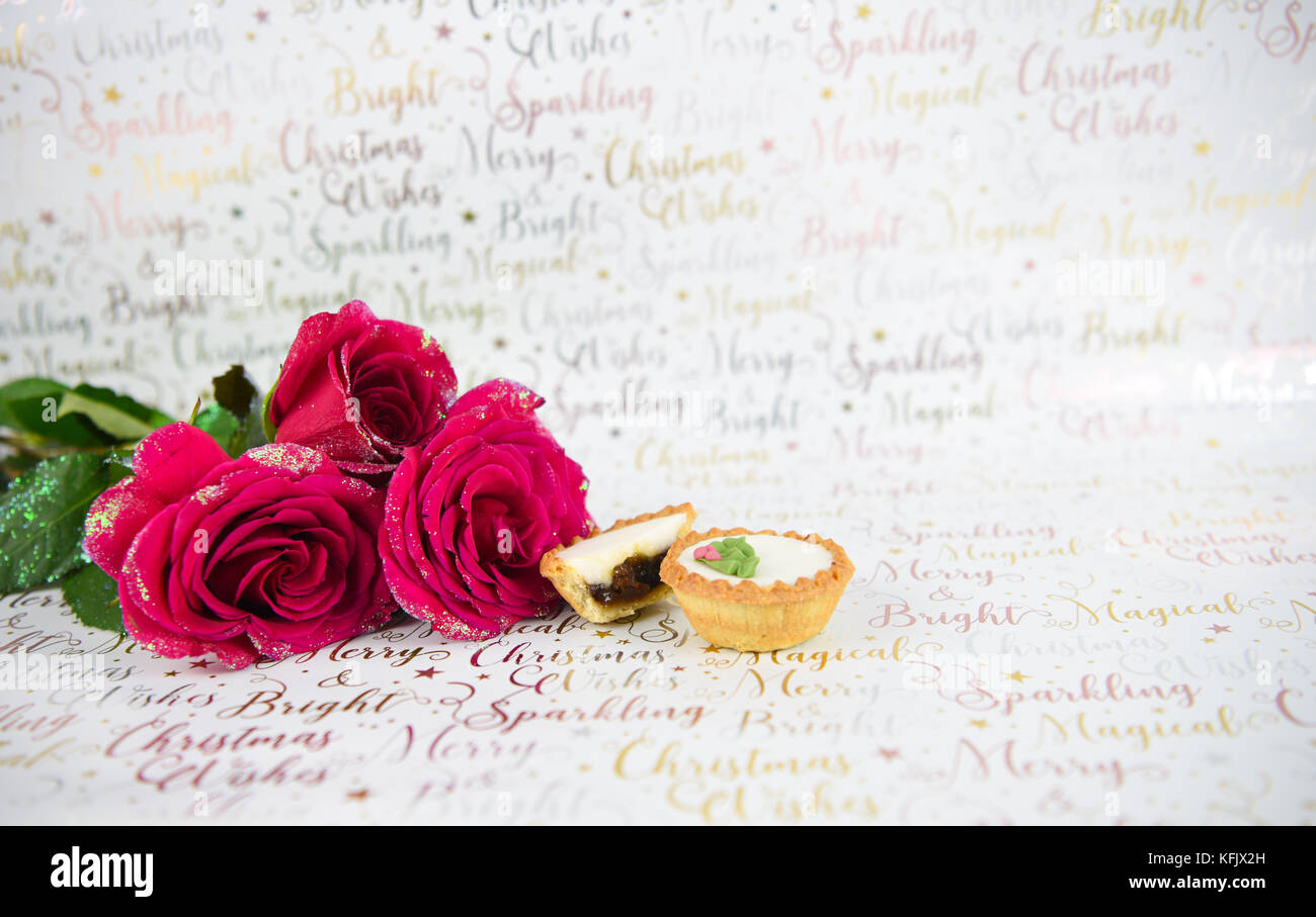 Christmas food photography image with xmas glitter red roses and iced mince pies on white shiny wrapping paper background with festive writing Stock Photo