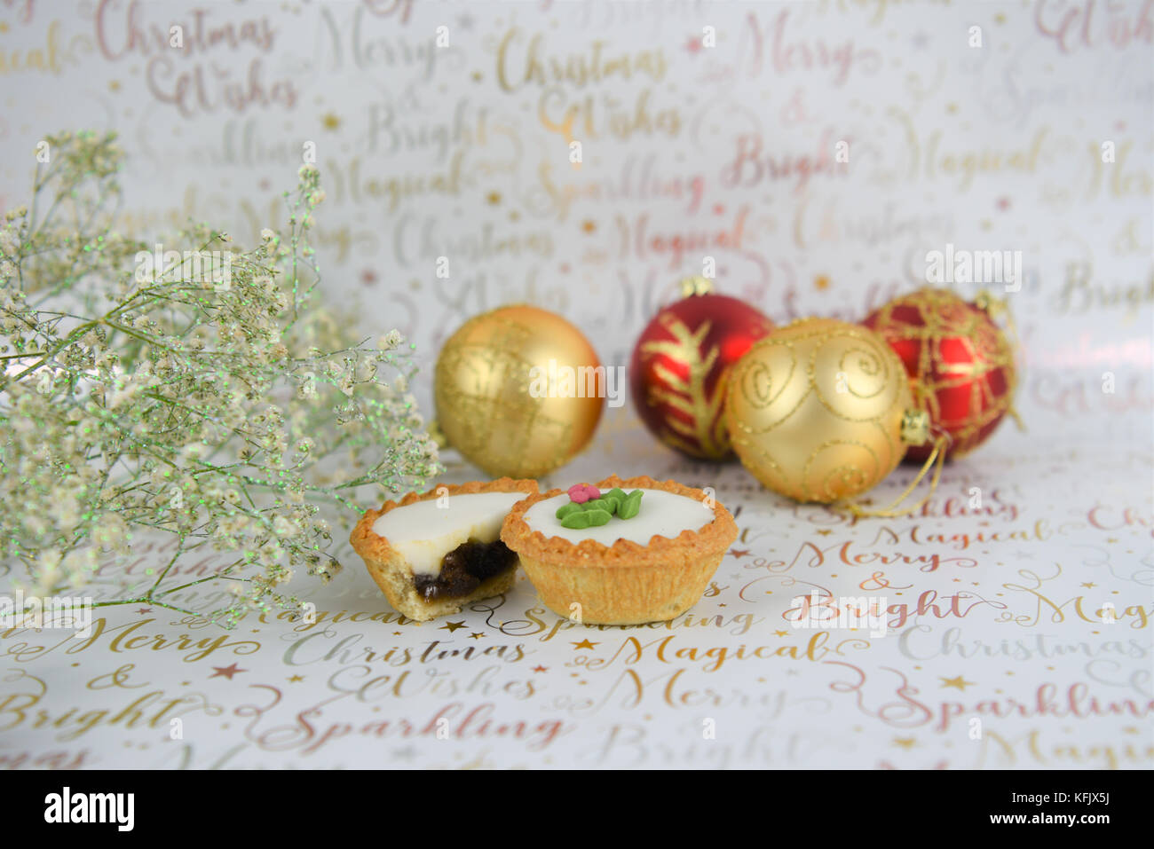 Christmas food photography image with glitter flowers red gold baubles and iced mince pies on white shiny festive Stock Photo