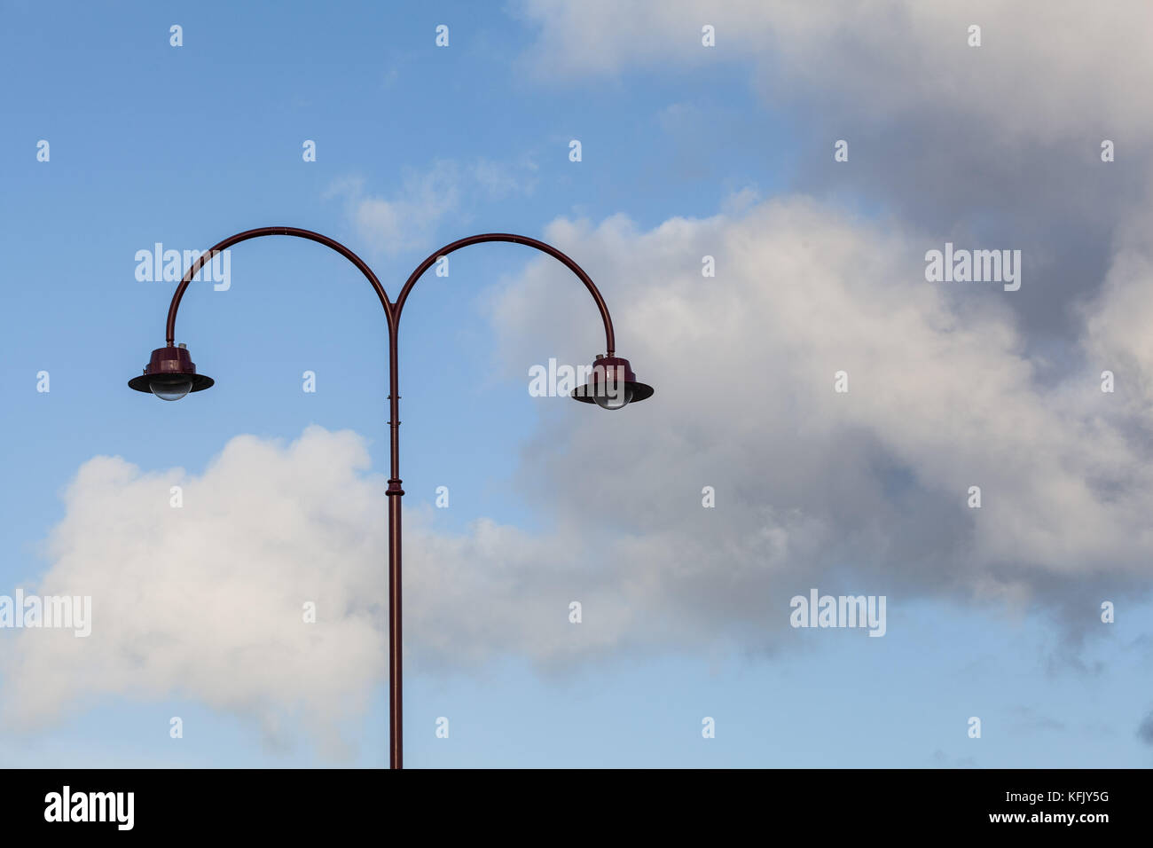 Vintage arched street light closeup on blue sky, fluffy clouds as background - Stock Image