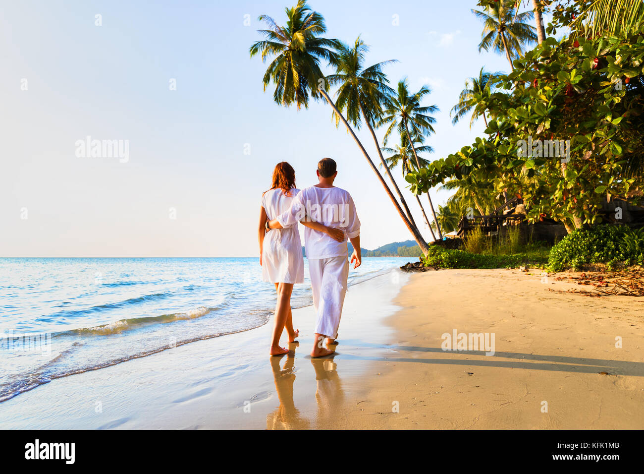 Romantic couple walking together on the tropical beach in warm sunny summer during honeymoon vacations - Stock Image
