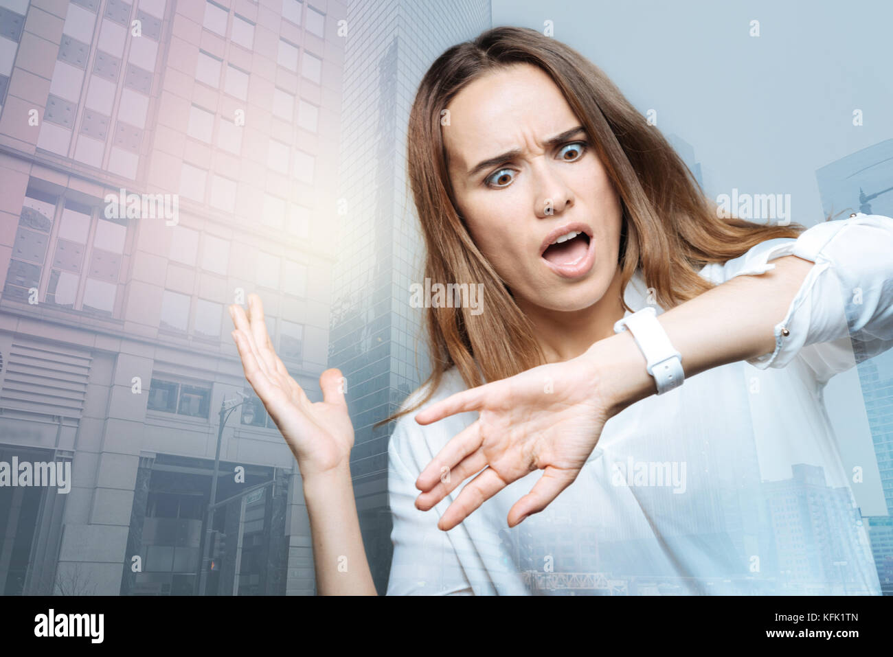 Unhappy surprised woman looking at her watch - Stock Image