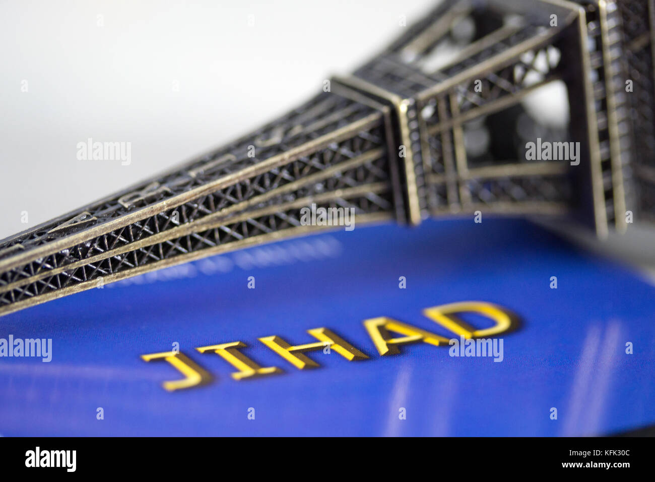 A small figurine of the Eiffel tower placed on its side & photographed with the words Jihad underneath. Concept - Stock Image