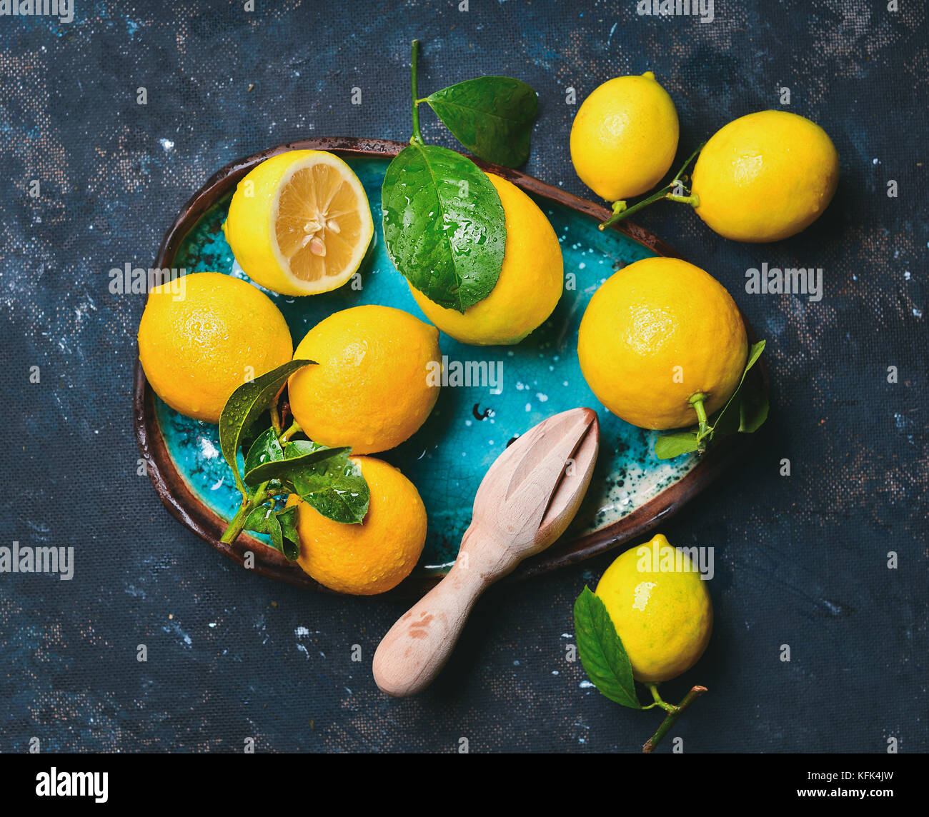Freshly picked lemons with leaves in blue ceramic plate - Stock Image