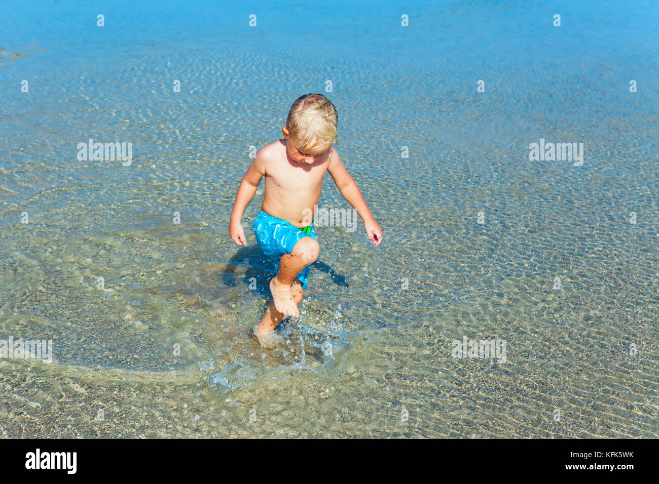 Happy family vacation. Positive child have fun - run and jump witn splashes by water pool on sand beach. Active - Stock Image