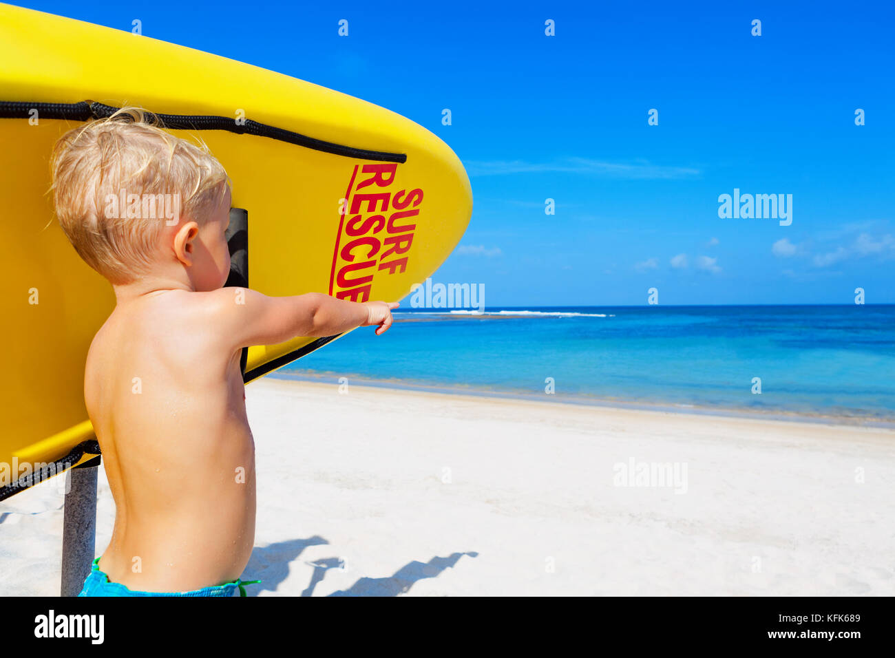 Life saving yellow board with surf rescue sign. Funny children lifeguard stand on duty, look at sea. Swimming people - Stock Image