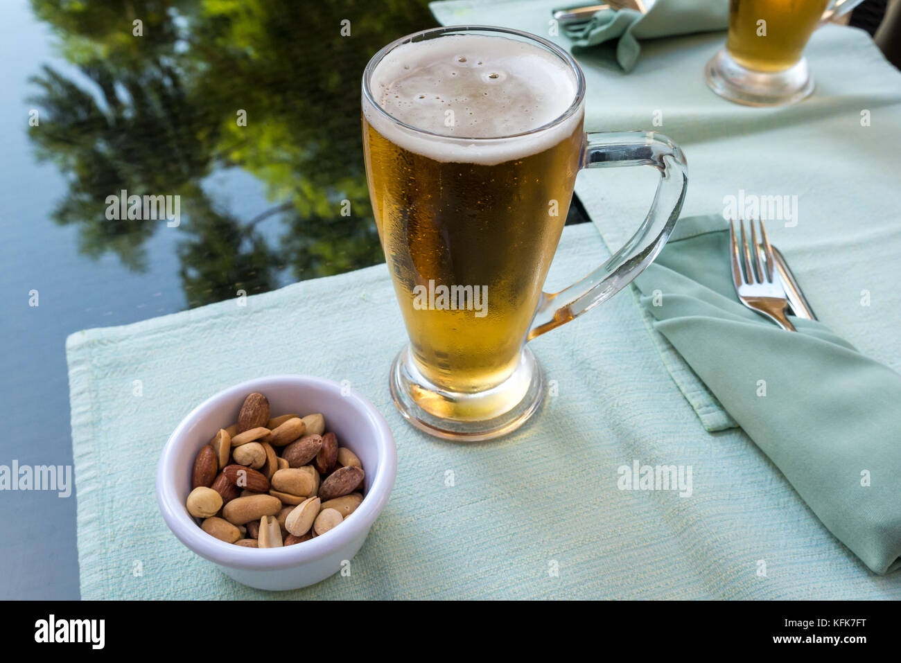 Close up of cold beer glass mugs and mixed nuts in small dish on glass lunch table with cutlery setting and blurred - Stock Image