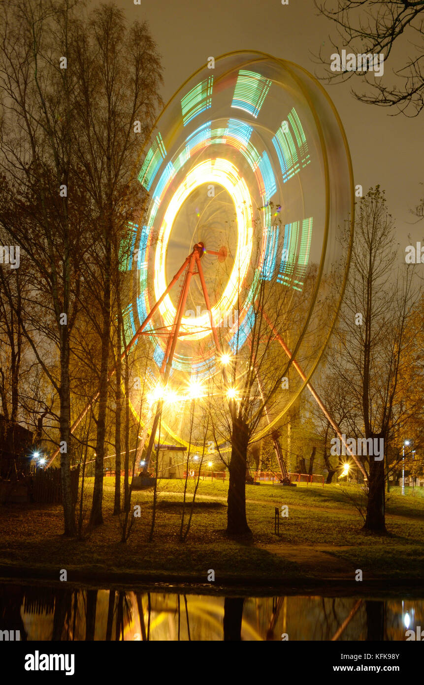 The Ferris wheel rotates and glows brightly at night. - Stock Image