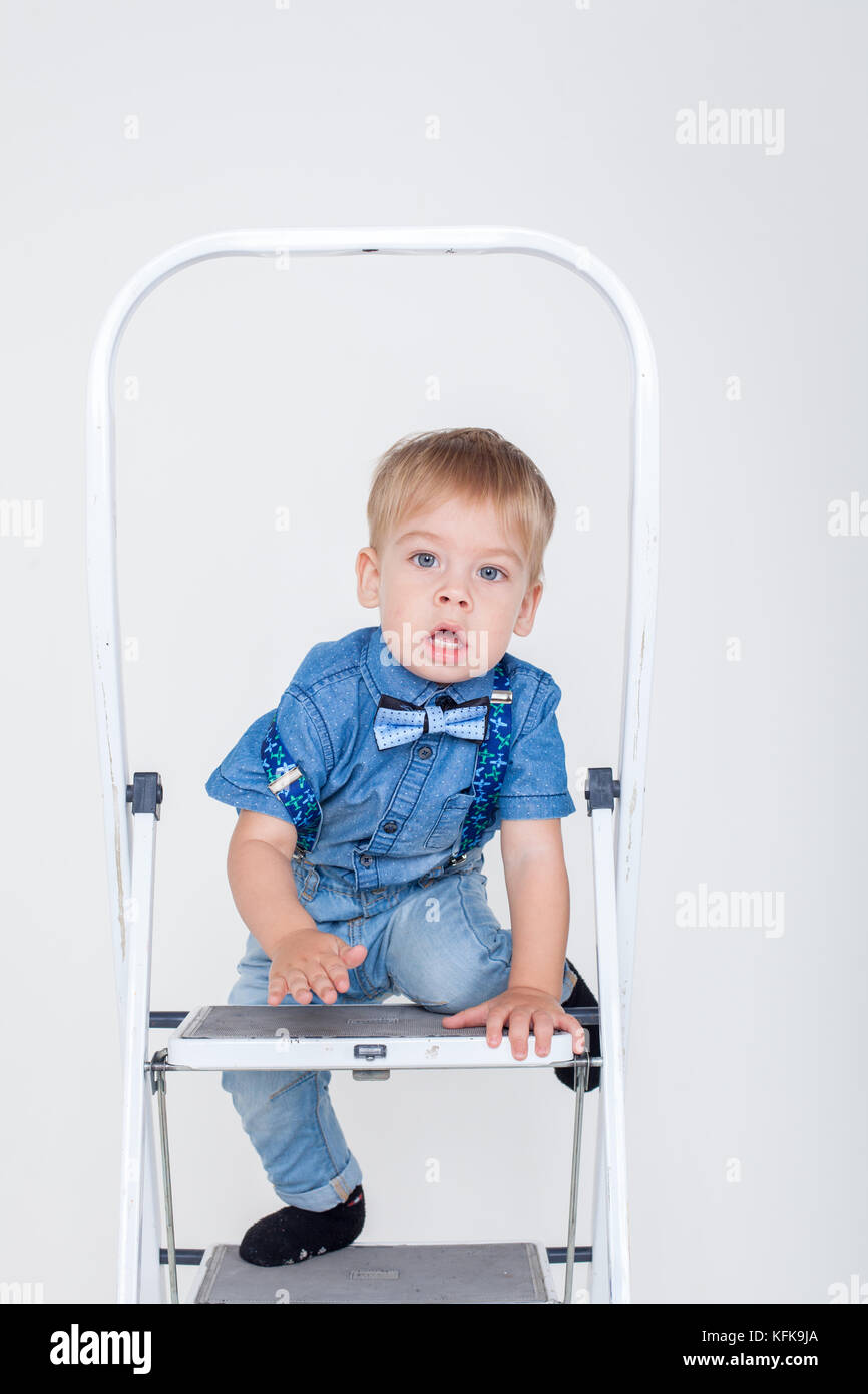 boy in a suit sitting on a stepladder - Stock Image