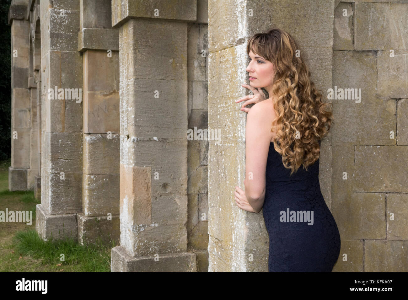 Lady looking around the columns on a portico Stock Photo