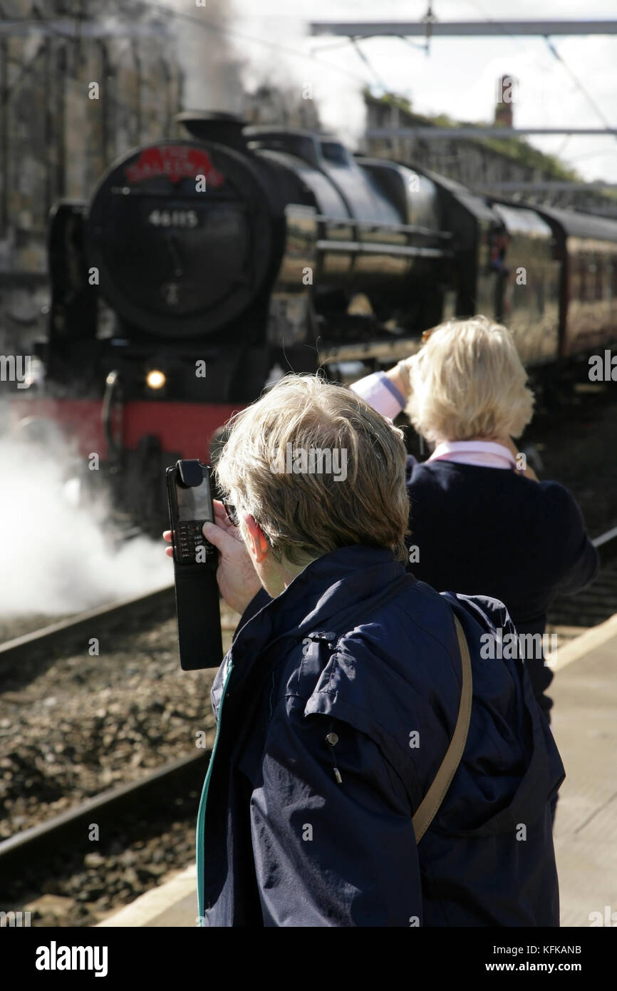 Passengers using phones to photograph LMS Royal Scot class 7P steam locomotive Scots Guardsman at Carlisle station, - Stock Image