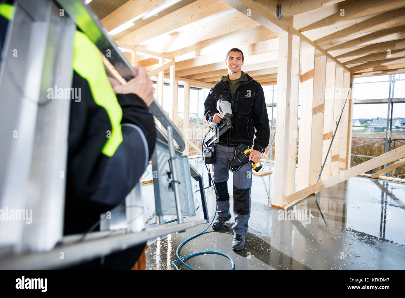 Carpenter Smiling While Female Colleague Carrying Ladder At Site - Stock Image