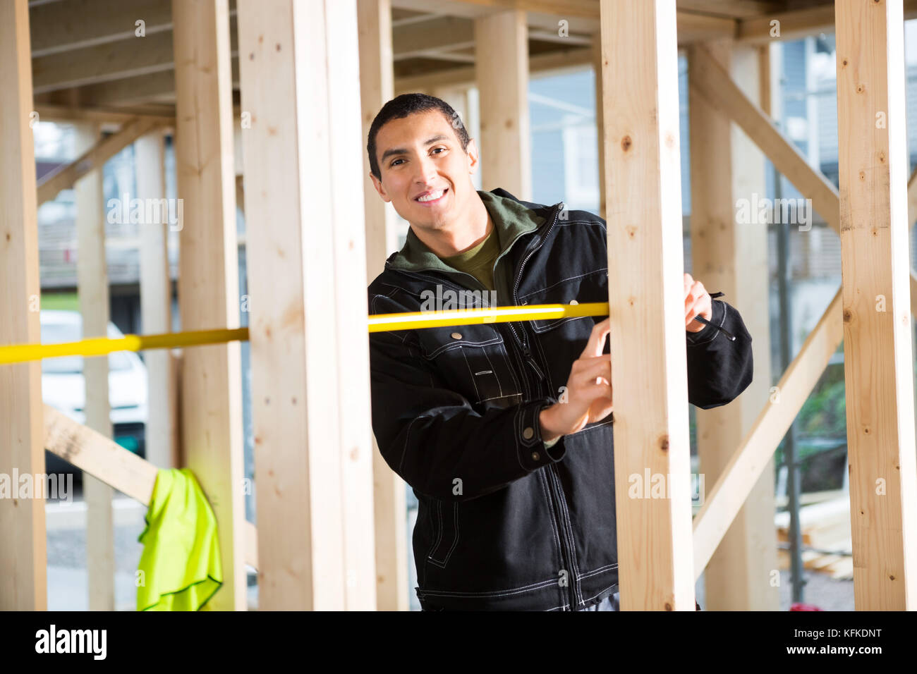 Young Carpenter Measuring Wood At Construction Site - Stock Image