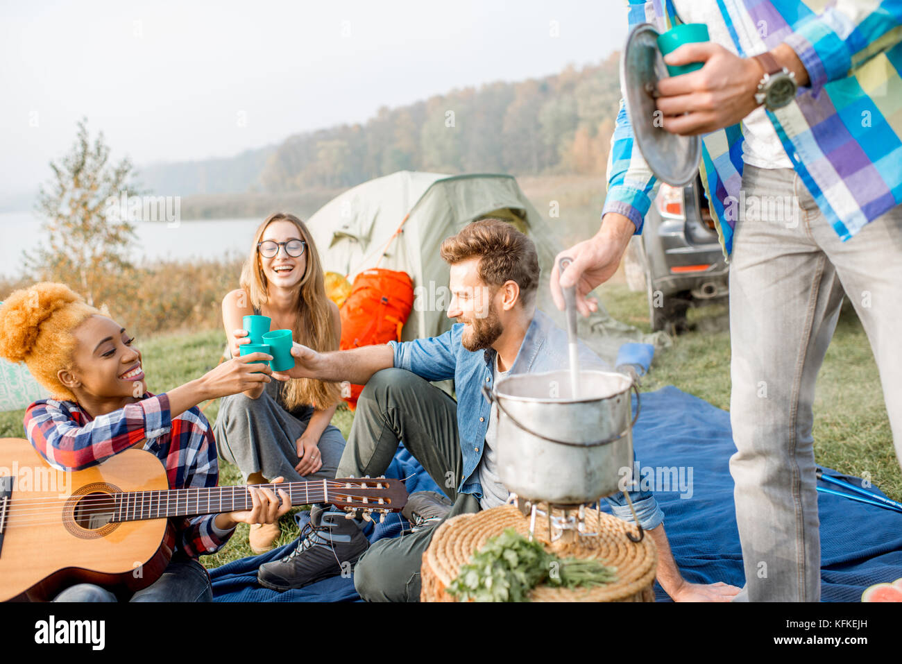 Multi ethnic group of friends dressed casually clinking glasses during the dinner outdoors at the camping - Stock Image