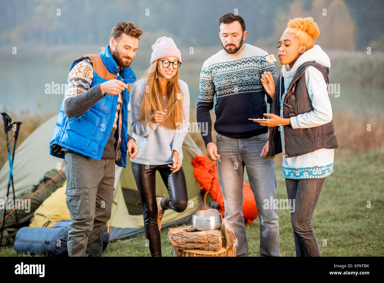 Friends in sweaters eating fondue outdoors - Stock Image