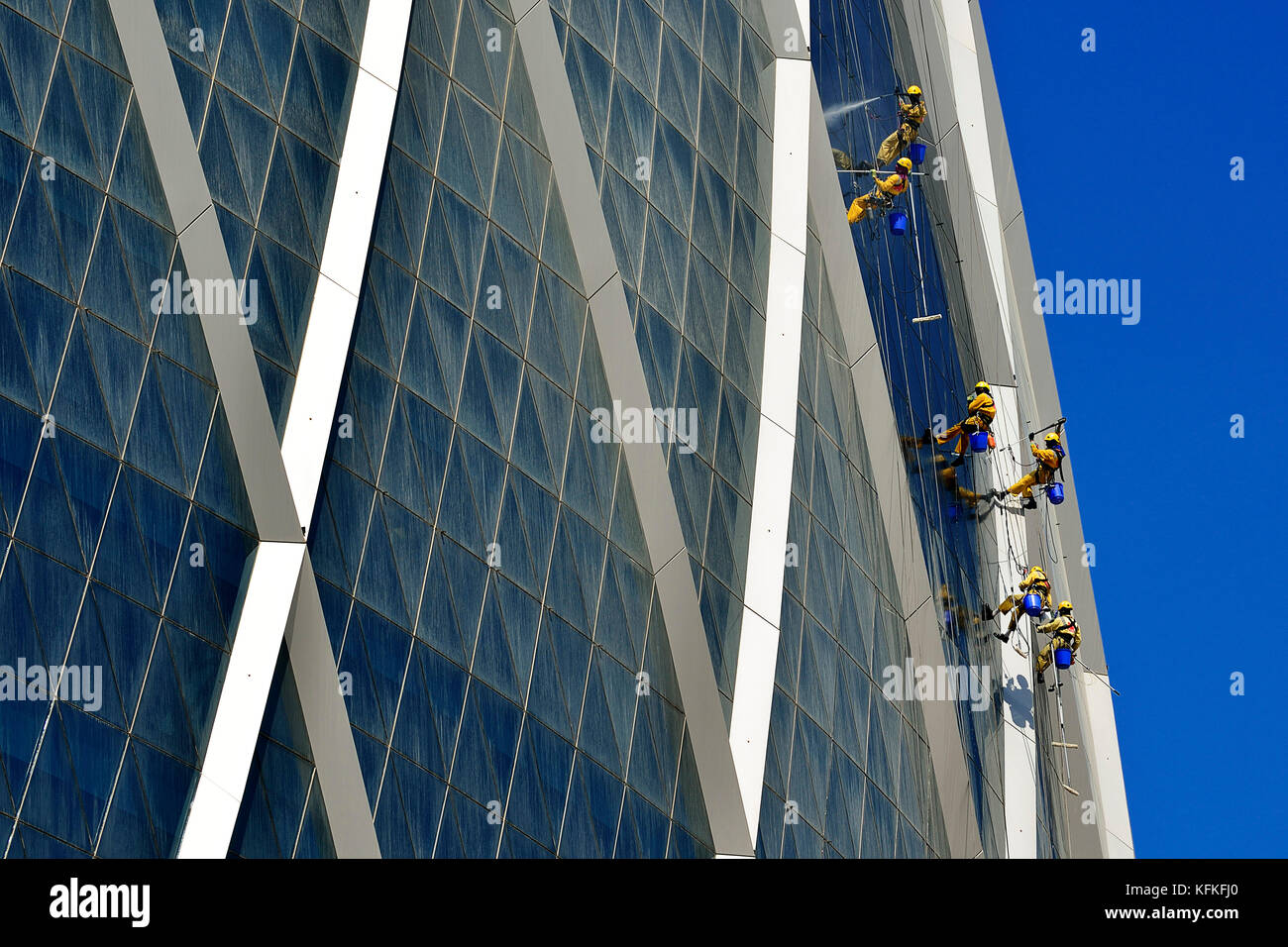 Window cleaners hang on The Coin building, headquarters of Aldar, one of the largest real estate companies in the - Stock Image