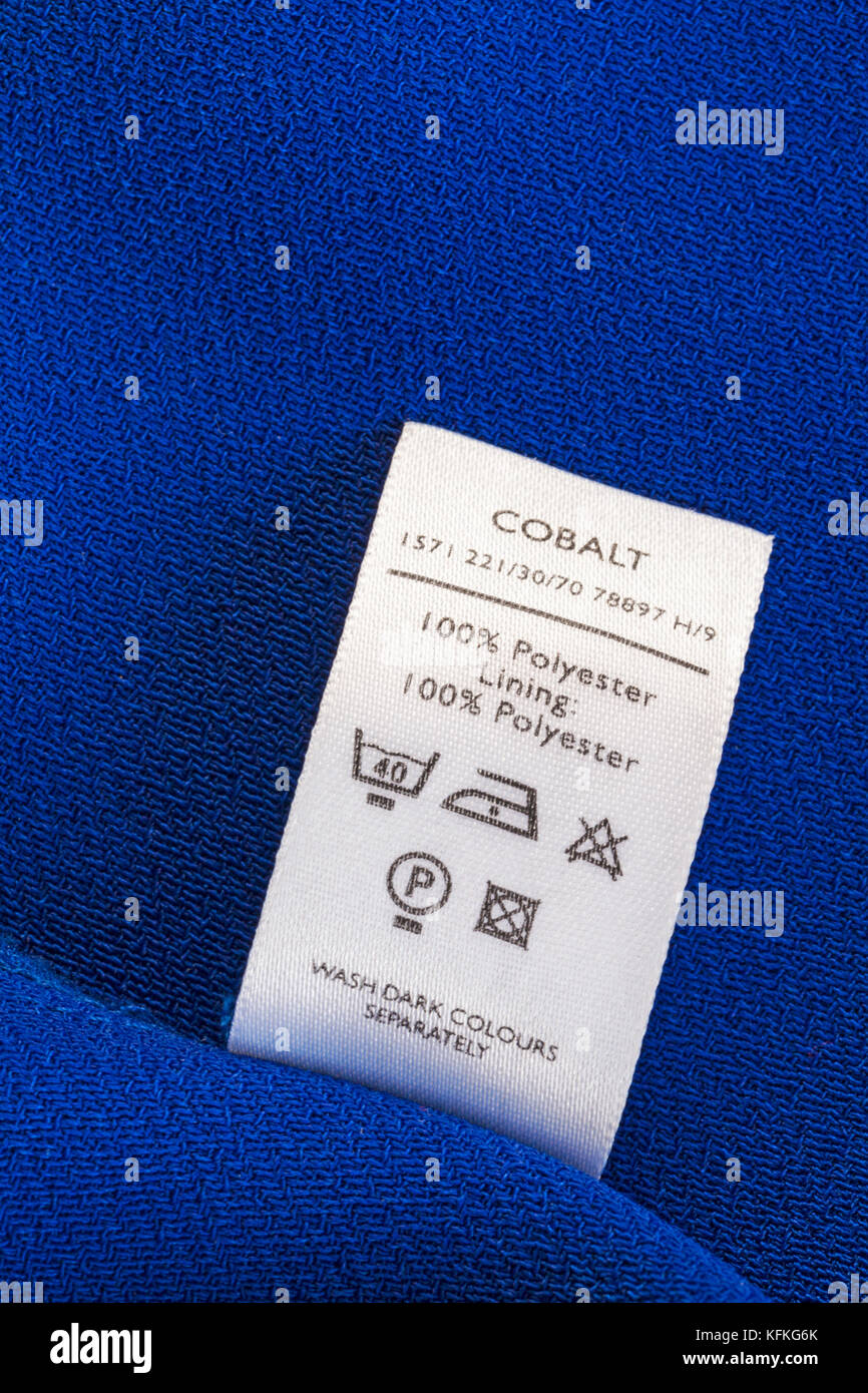 100% polyester lining 100% polyester label in woman's cobalt jacket with care washing instructions symbols  - Stock Image