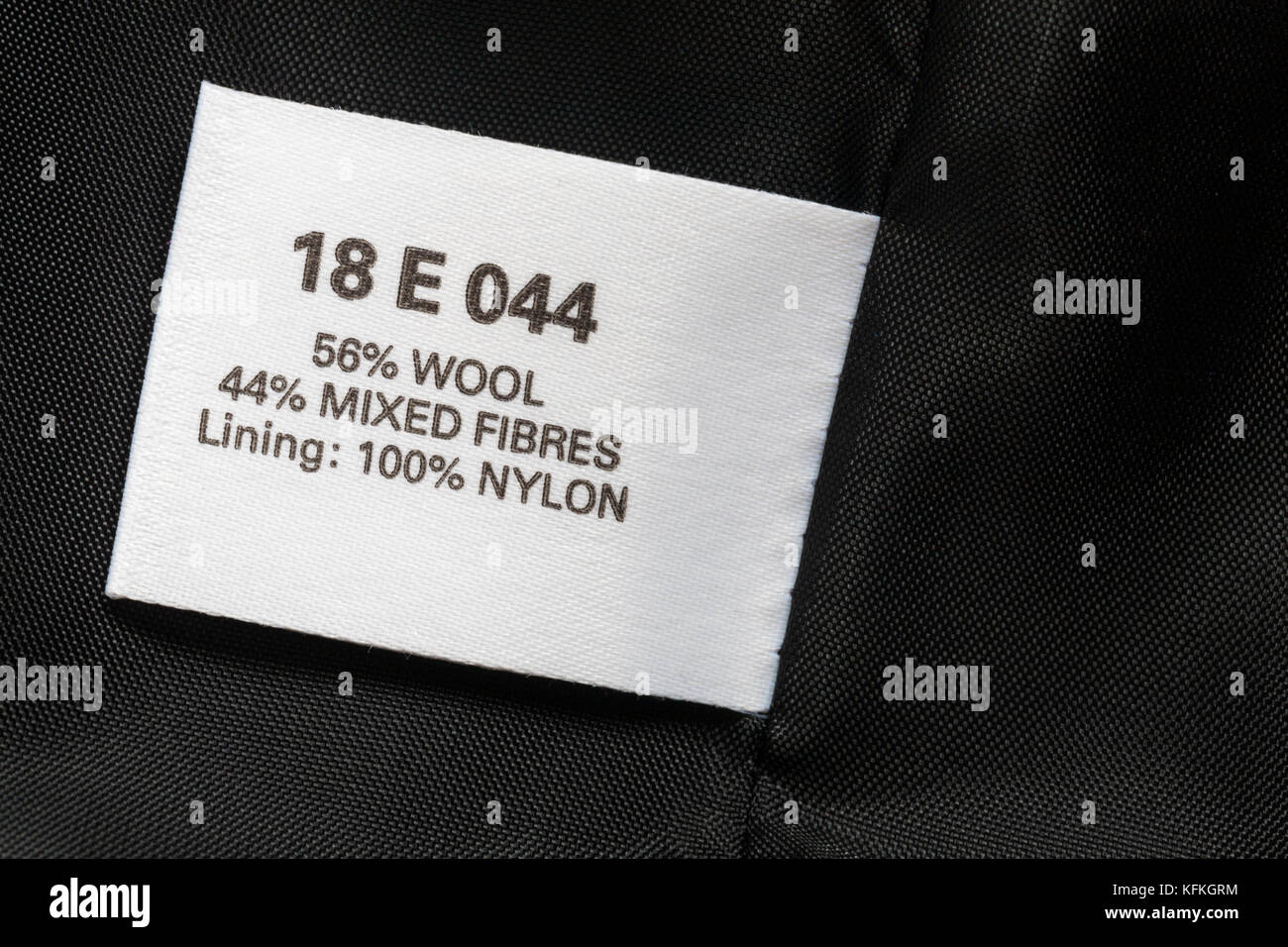 56% wool 44% mixed fibres lining 100% nylon label in woman's jacket - Stock Image