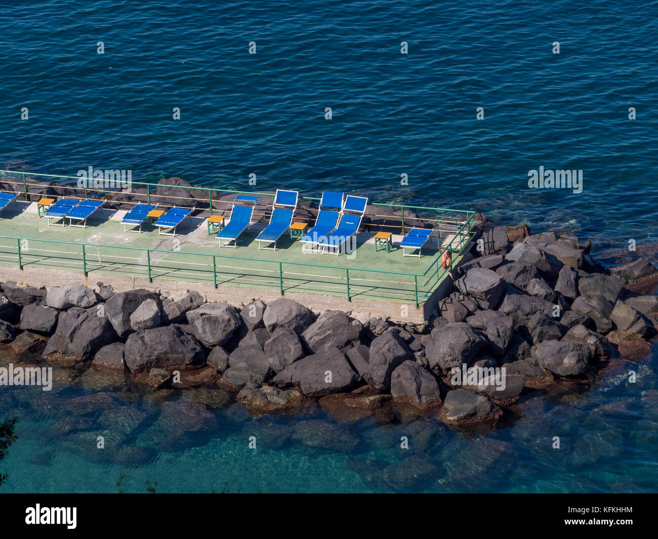 Empty sun loungers on sunbathing deck surrounded by the Mediterranean Sea. Sorrento, Italy. - Stock Image