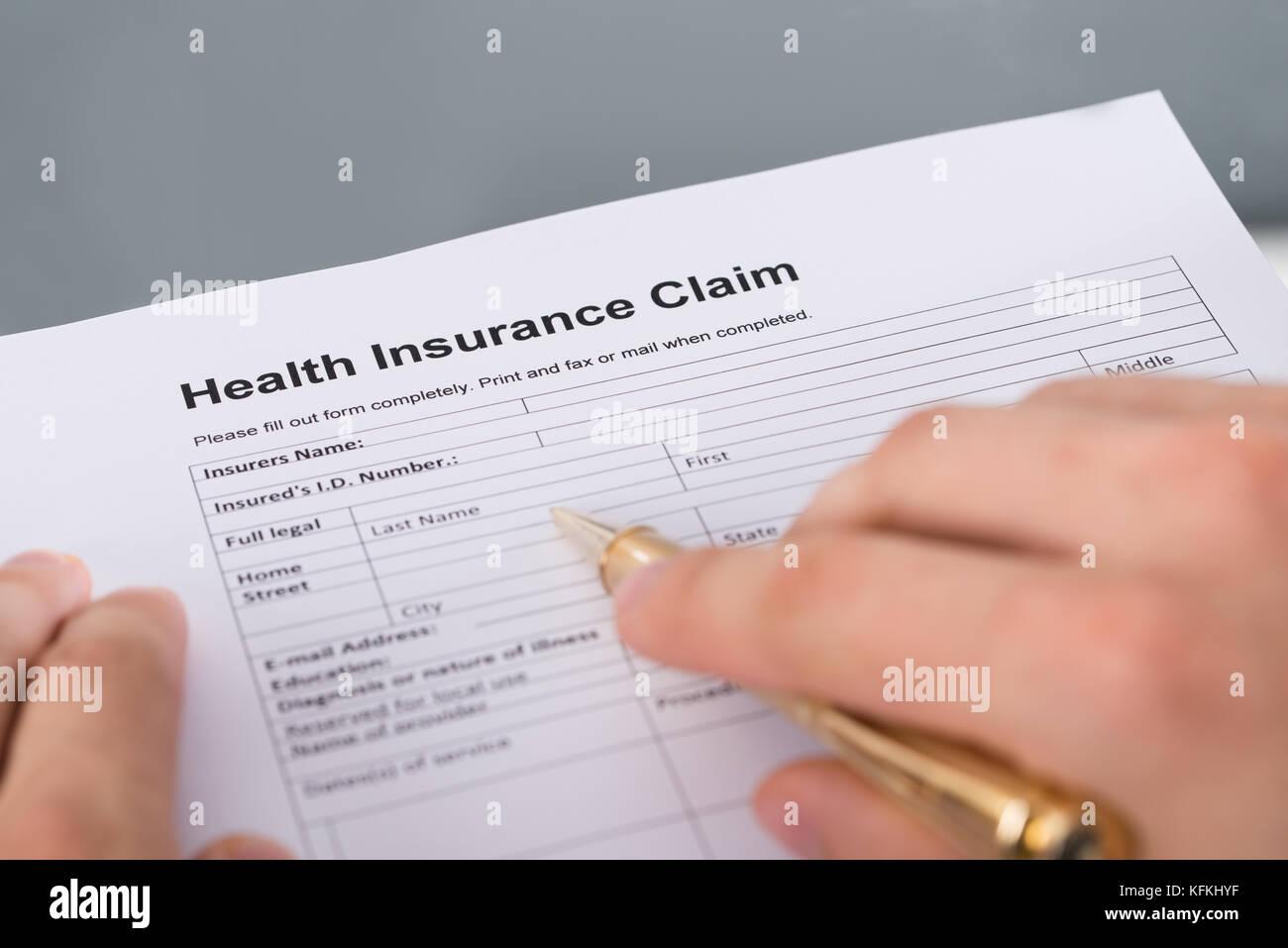 Hand filling health insurance claim form. Closeup shot - Stock Image