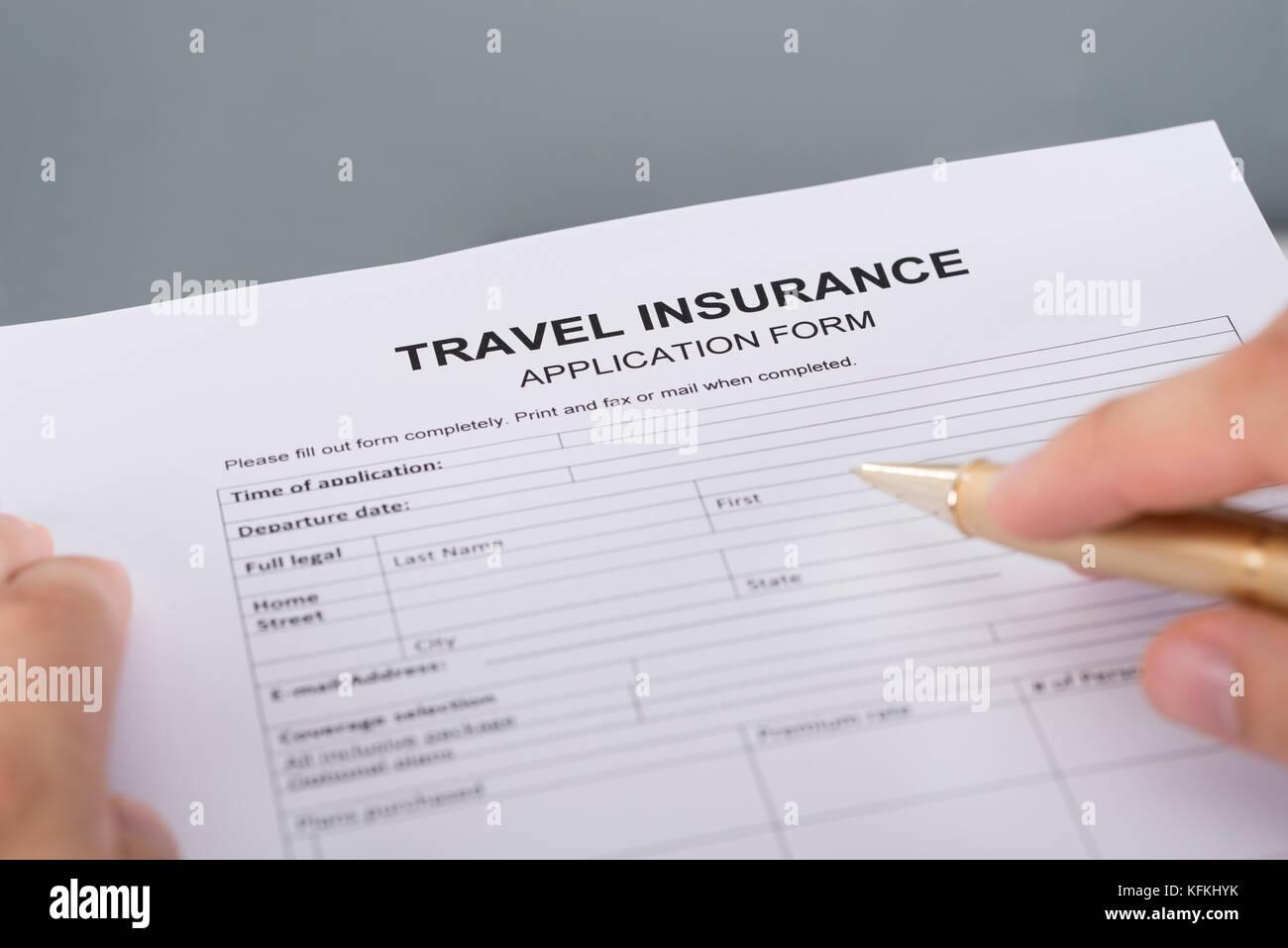 Hand filling travel insurance form. Closeup shot - Stock Image