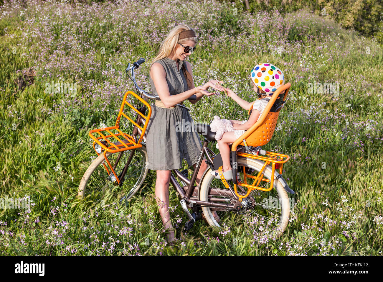 LOS ANGELES, CA – JULY 11: Woman rides a bicycle on a path over looking the ocean in Los Angeles, California on Stock Photo
