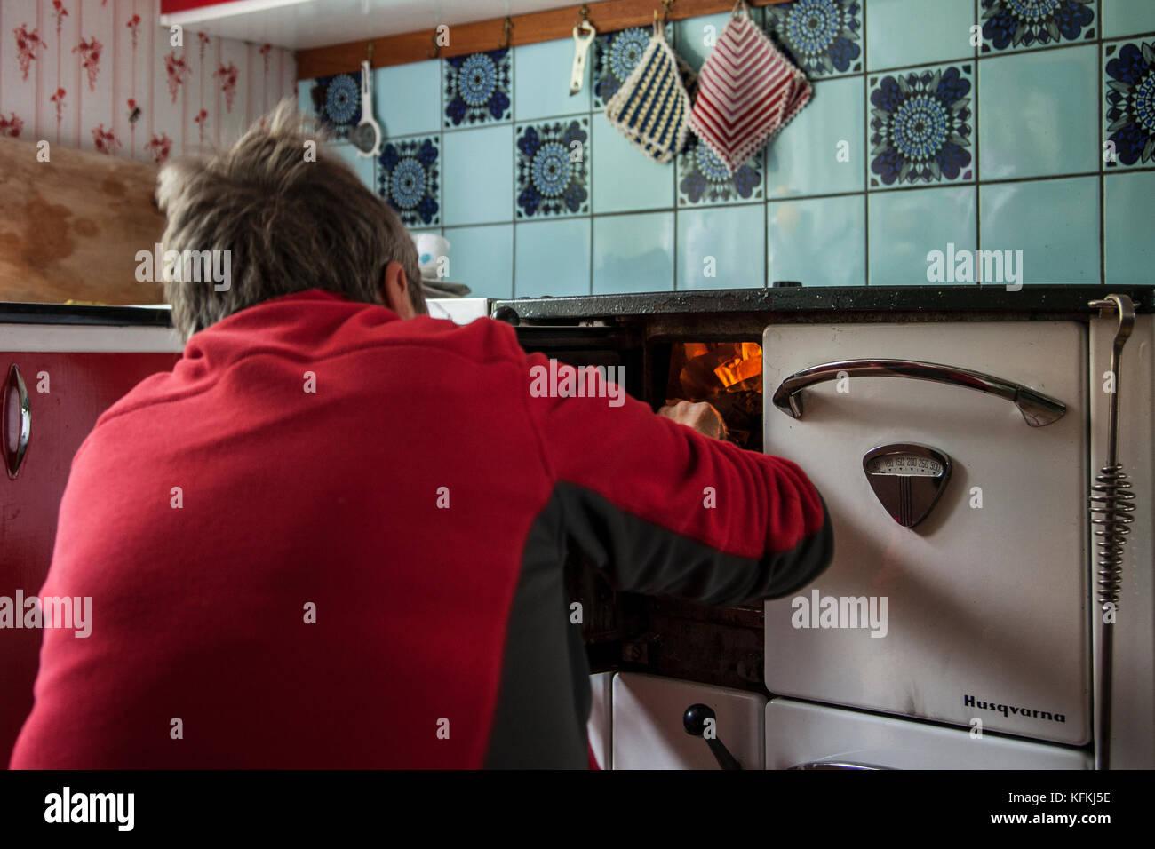 Kvinna tänder vedspisen / Woman lights the wood stove - Stock Image