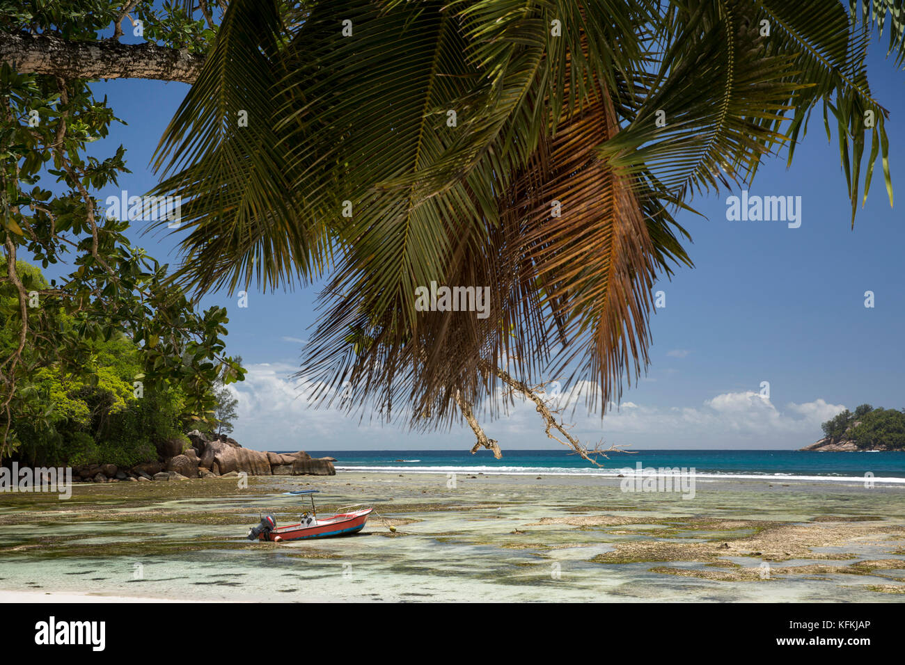 The Seychelles, Mahe, Baie Lazare, beach, boat in lagoon at low tide - Stock Image
