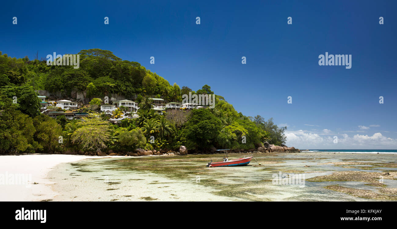 Sey247	The Seychelles, Mahe, Baie Lazare, beach, boat in lagoon at low tide below properties on headland panoamic - Stock Image