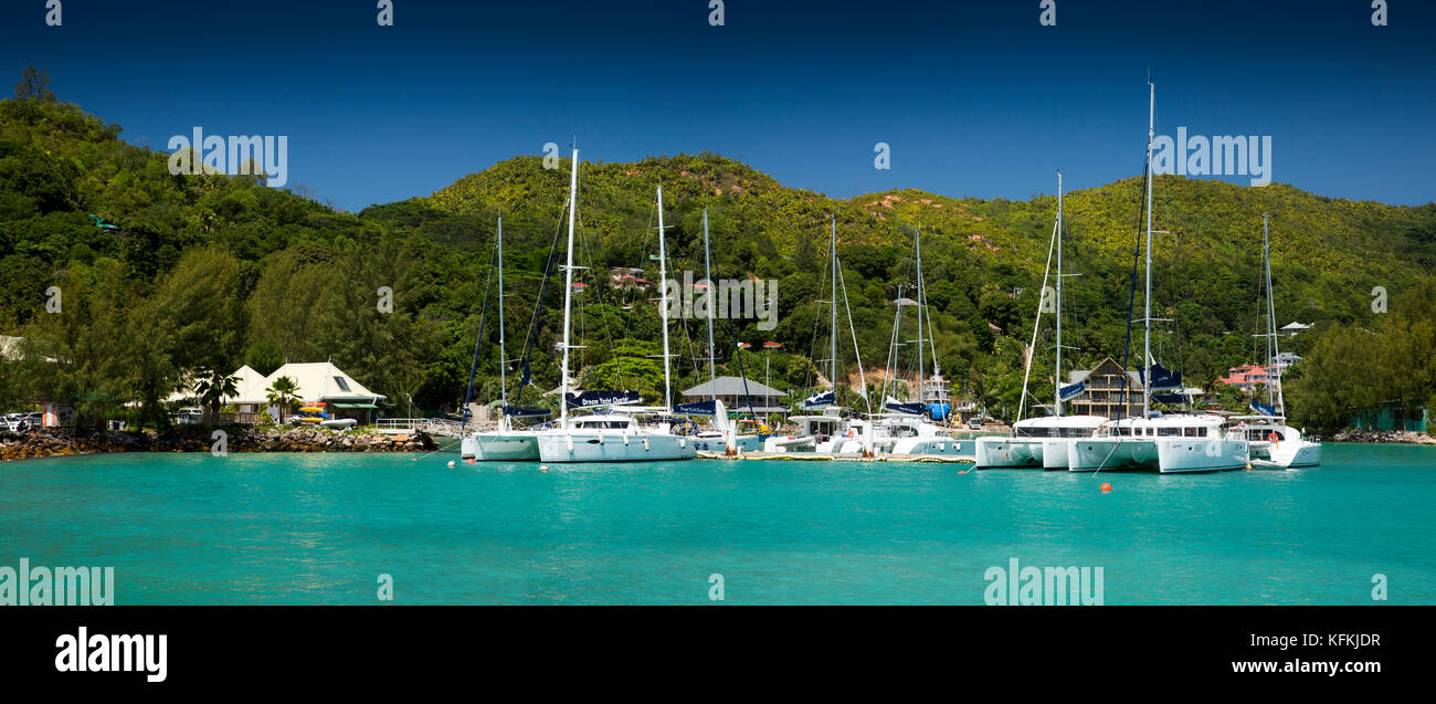 The Seychelles, Praslin, Baie St Anne, jetty, charter boats moored in sheltered harbour, panoramic Stock Photo