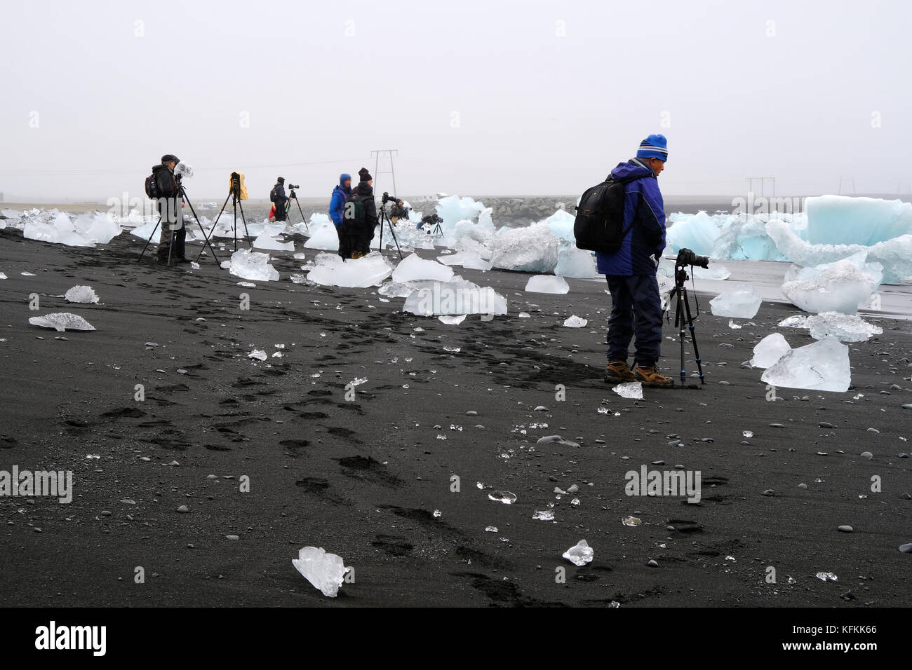 Photographers on photo tour with cameras and tripods standing and photographing icebergs washed up on black sand - Stock Image