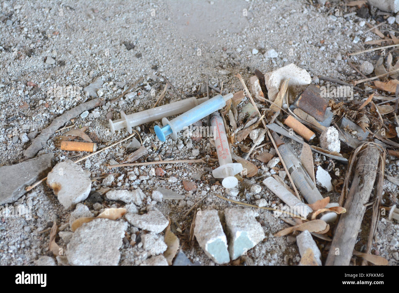 Discarded syringe and on ground used by heroin addict. - Stock Image