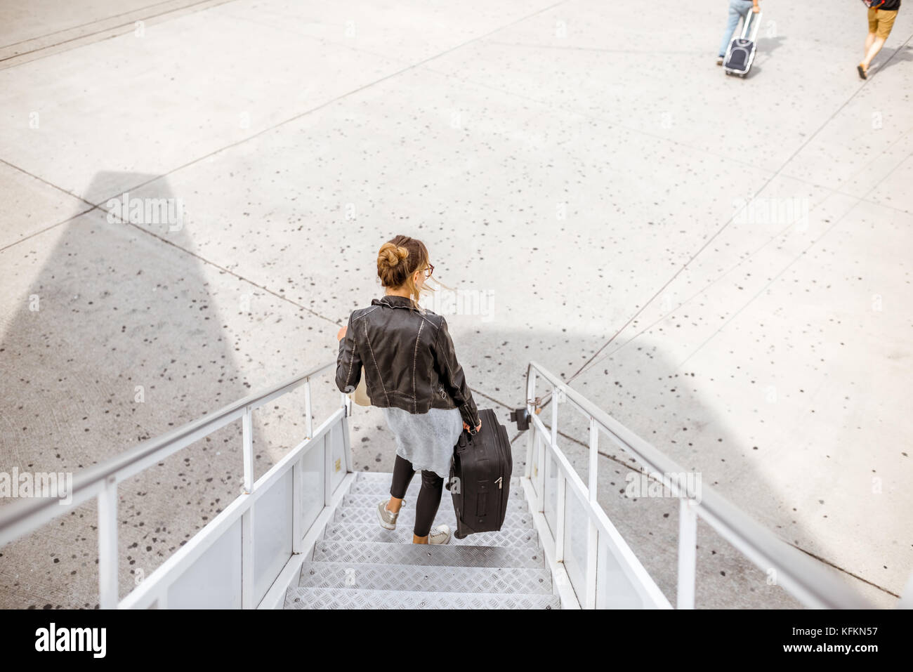 Woman walking out the airplane - Stock Image