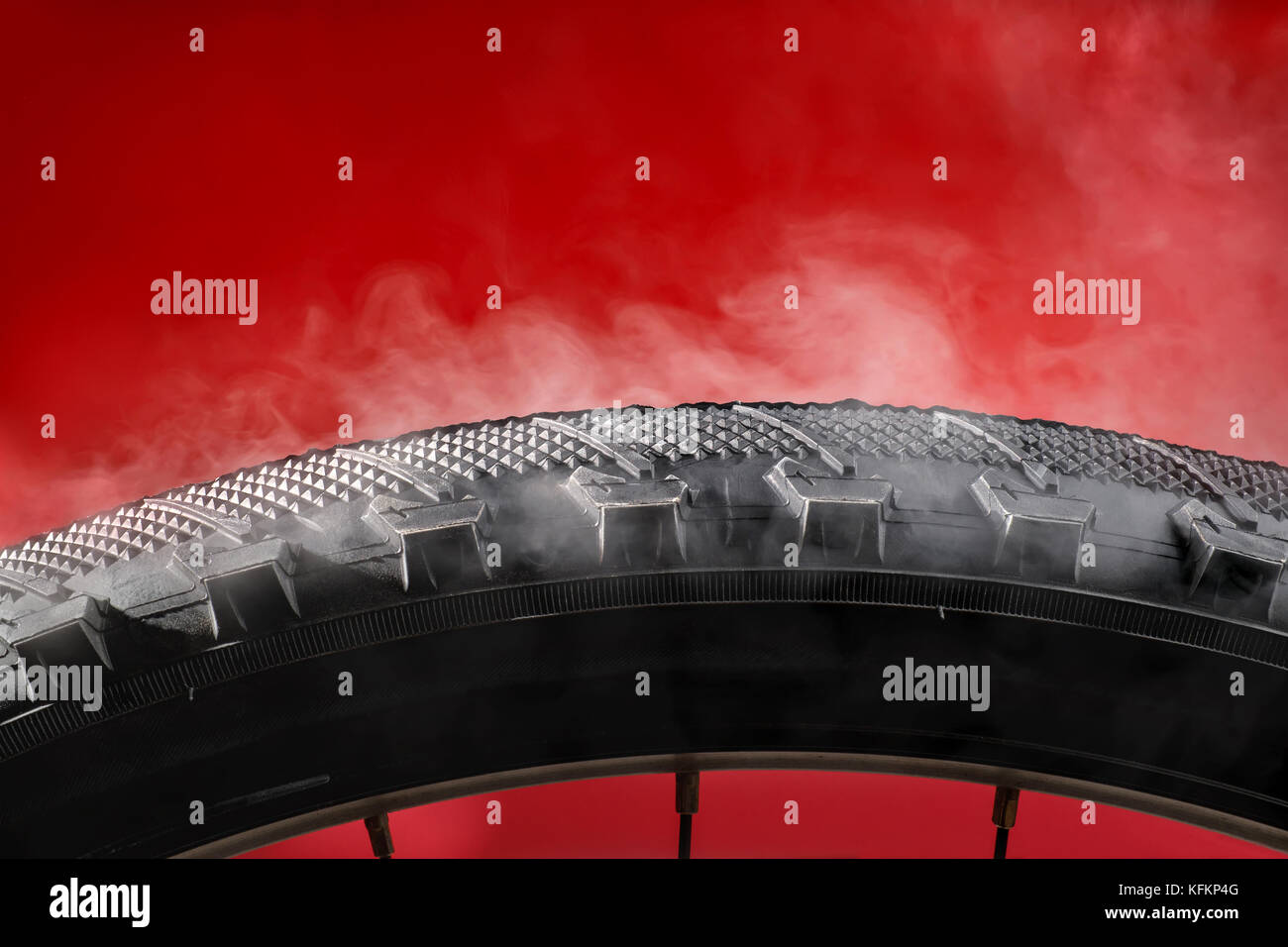 Smoking bike tire. On red background - Stock Image