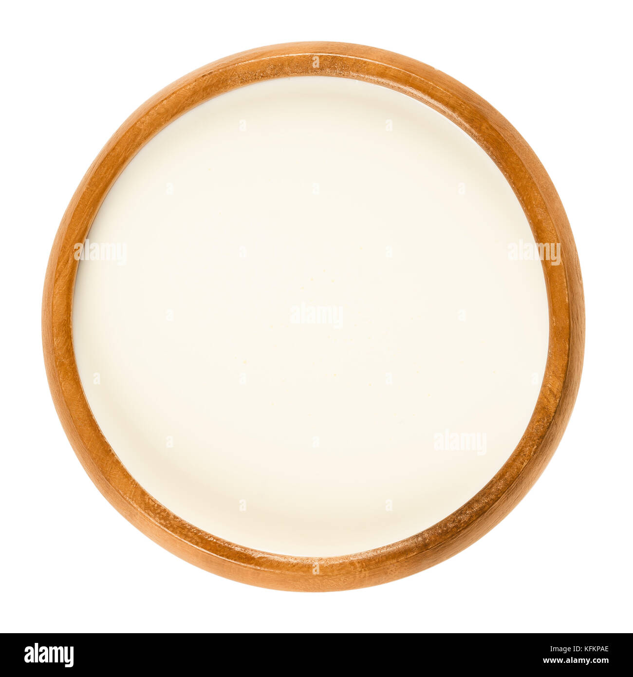 Fresh sweet cream in wooden bowl, a dairy product composed of the higher butterfat layer skimmed from the top of - Stock Image