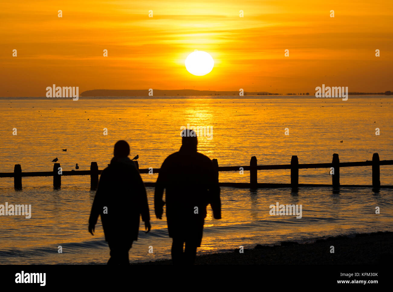 A couple walking on the beach as the sun goes down over the sea in Autumn in the UK. - Stock Image