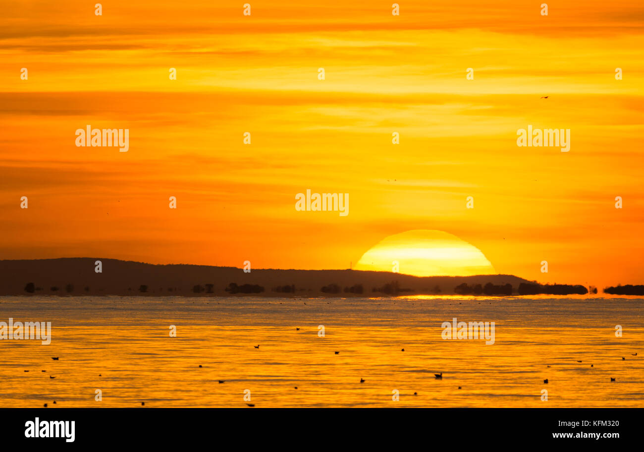 Sun setting over the ocean and disappearing below the horizon, with red and orange sky in Autumn in the UK. - Stock Image