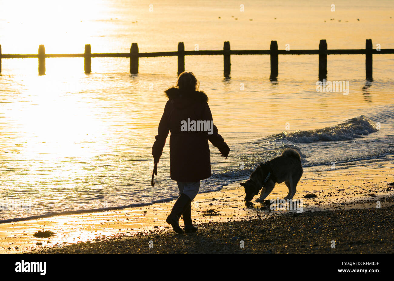 Woman walking a dog on the beach as the sun goes down in Autumn in the UK. - Stock Image