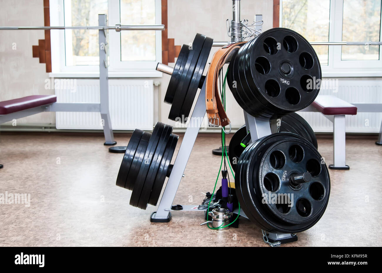 Disassembled barbell on floor in gym.Sports equipment - Stock Image