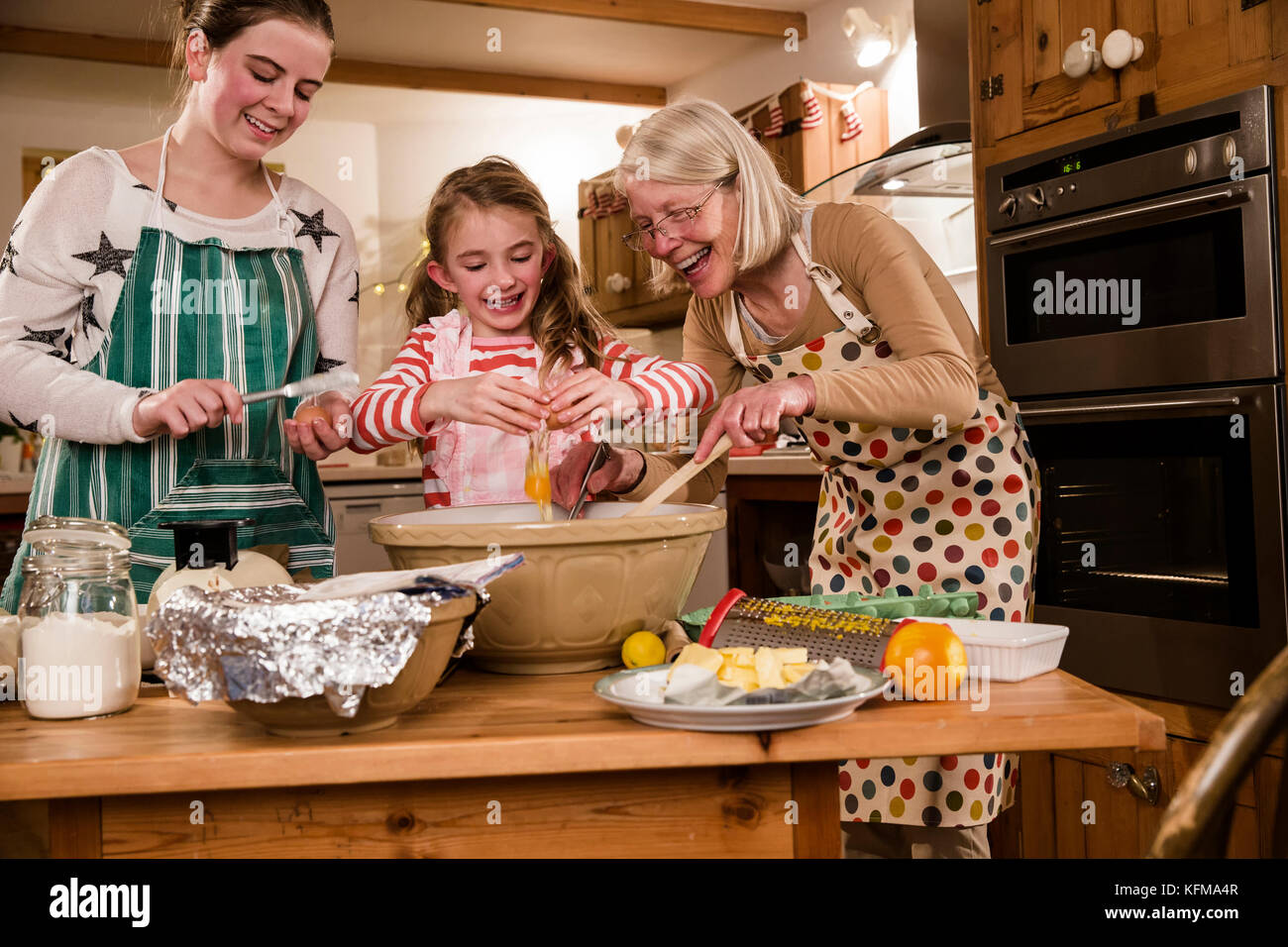 Two sisters are baking cakes in the kitchen with their ...