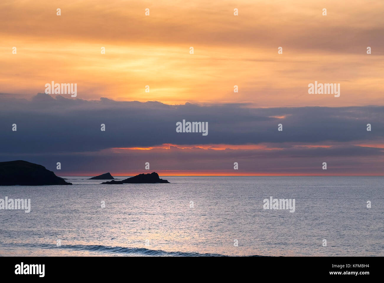 Spectacular sunset - The Goose and The Chick small islands off East Pentire Headland are seeen in silhouette as Stock Photo