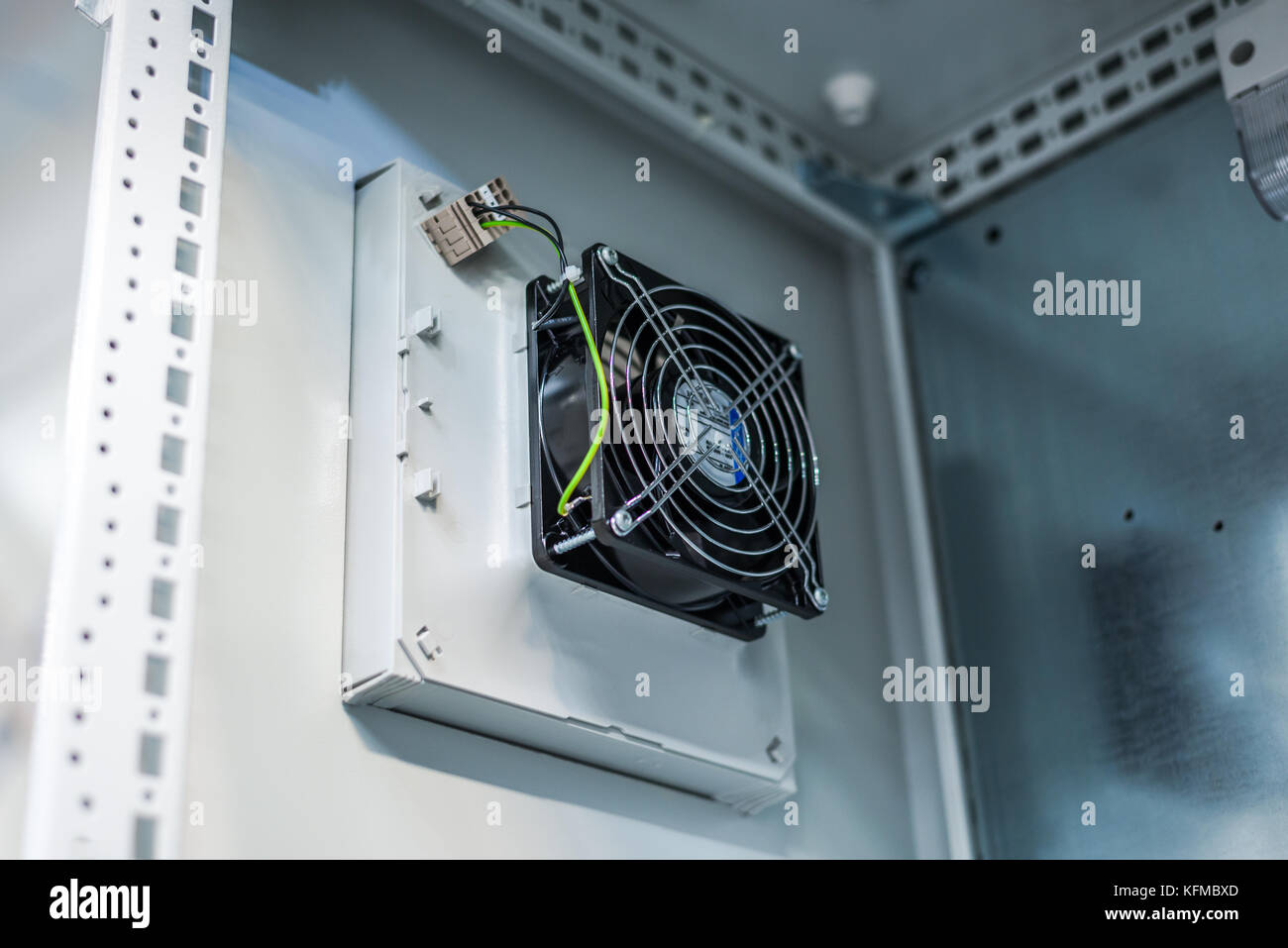 Electric cooling fan in industrial enclosure, power distribution industry. - Stock Image