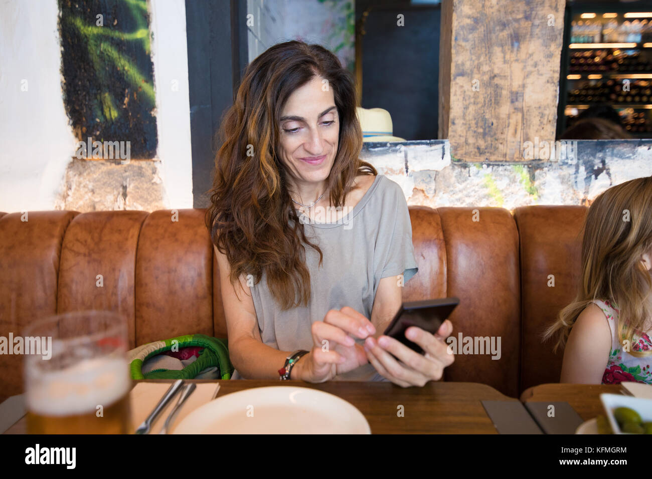 woman mother in restaurant, touching and watching smartphone, sitting next to four years age blonde girl - Stock Image